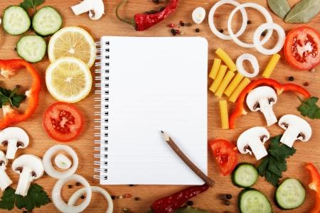 筆記本食譜,蔬菜和香料的木桌上。