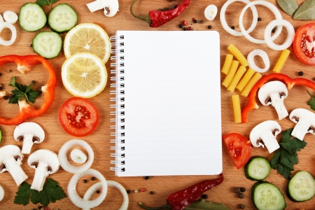 Notebook for recipes, vegetables and spices on wooden table. Stock Photo - 17512602