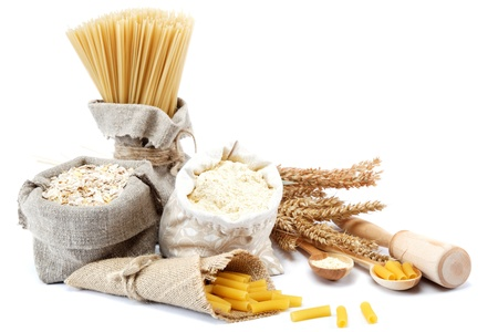 Flour, cereals, pasta in a canvas bag and ear on white background. photo