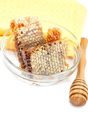 Honey comb in a glass bowl and wooden stick, isolated on white background. Stock Photo - 17943949