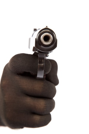 weaponry: Hand in black glove holding a gun on a white background. Stock Photo