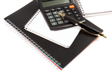 Calculator, pen and notebook on a white background. photo