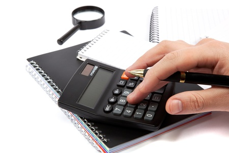Hands holding the handle and pressing calculator buttons over documents. Stock Photo - 18140089