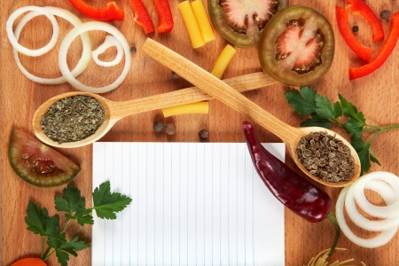 Notebook for recipes, vegetables and spices on wooden table. photo