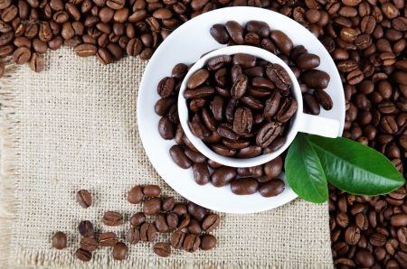 Cup with coffee beans on sackcloth. photo