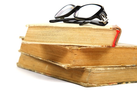 bezel: Stack of old books and glasses on a white background. Stock Photo