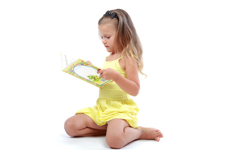 Cute little girl with an open book isolated on a white background. photo