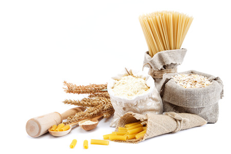 Flour, cereals, pasta in a canvas bag and ear on white background.