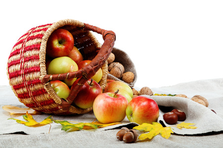 Autumn theme. Apples in a basket and walnuts on linen canvas. photo