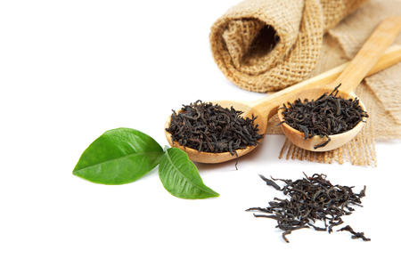 plant antioxidants: Black tea in a wooden spoon and green lemon leaves isolated on a white background.