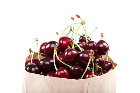 Fresh cherry fruit in a paper bag isolated on a white background.
