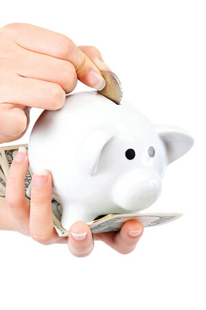 Beautiful female hands putting coin into piggy bank isolated on a white background. 版權商用圖片