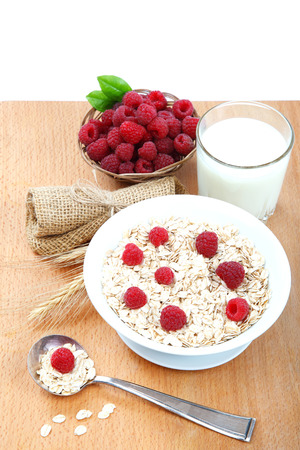 Fresh raspberries, Oatmeal flakes and milk on a wooden table. Healthy food.  photo