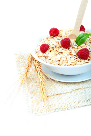 Fresh raspberry and Oatmeal flakes isolated on white background. Healthy food.  photo
