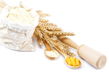 Flour in a canvas bag and ear on white background. photo