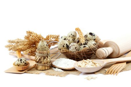 Quail eggs, flour and cooking utensils on canvas isolated on white background. photo