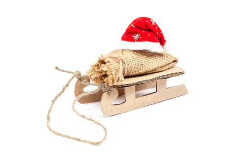 Sleigh with a sack and a Santa Claus hat isolated on white background. photo