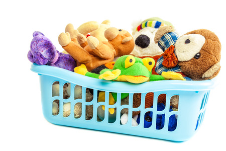 Soft toys in a plastic container isolated on white background. Standard-Bild