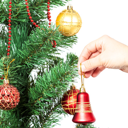 Female hand with red bell and Christmas tree isolated on white background. photo