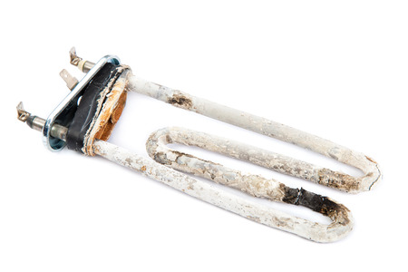 limescale: Damaged heating element of the washing machine isolated on white background. Stock Photo