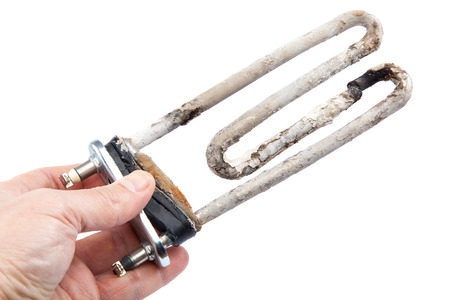 Damaged heating element of the washing machine in a hand on a white background. Stock Photo