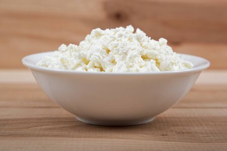 queso blanco: Fresh cottage cheese in a white bowl on a wooden table.