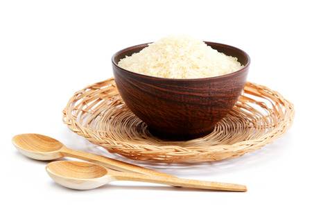 Grains of rice in a bowl and wooden spoon isolated on white background.