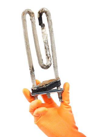 limescale: Damaged heating element of the washing machine in hand with rubber gloves isolated on white background. Stock Photo