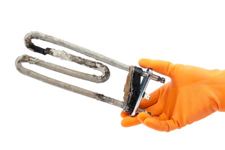 fruit water: Damaged heating element of the washing machine in hand with rubber gloves isolated on white background. Stock Photo