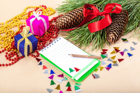note pad: Christmas gifts, note pad, pencil and spruce branches.