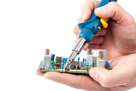 Soldering iron in hand and electric board isolated on a white background.