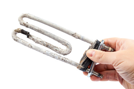 Damaged heating element of the washing machine in a hand on a white background. Standard-Bild
