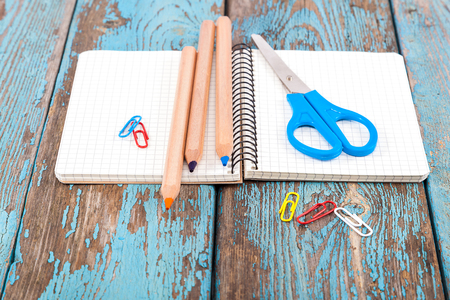 Notepad, pencils, scissors, paper clips. Office or school supplies on wooden planks painted in blue.