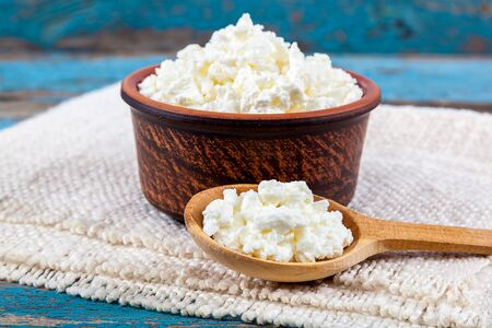 cottage: Fresh cottage cheese in a ceramic dish and spoon on painted blue wooden boards. Stock Photo