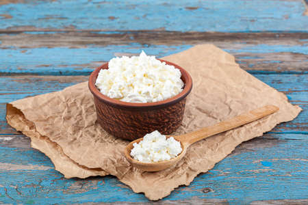 wooden spoon: Fresh cottage cheese in a ceramic dish and spoon on painted blue wooden boards. Stock Photo