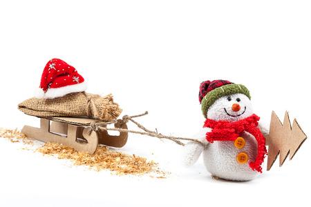 trineo: Muñeco de nieve con el trineo, árbol de Navidad y Santa Claus ropa aislados sobre un fondo blanco.