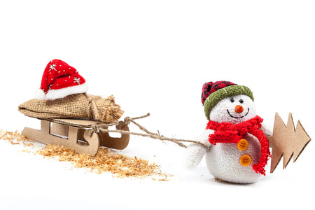 Snowman with sledge, Christmas tree and Santa Claus clothes isolated on a white background. Stock Photo