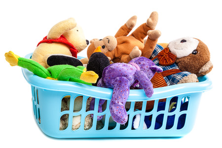 juguetes: cesto de la ropa de plástico con juguetes de peluche aislados en un fondo blanco.