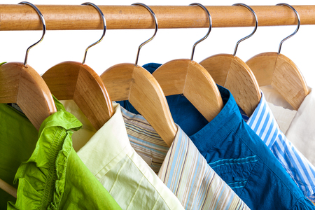 closet rod: Clothes on wooden hangers isolated on white background.