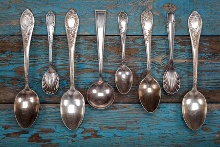 grunge flatware: German silver spoon and fork on a wooden background. Kitchen utensils.