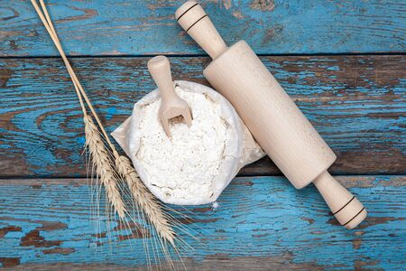 Flour in a canvas bag and wheat ears on a blue wooden background.
