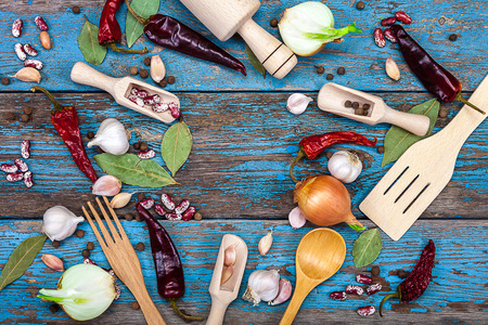 bay leaf: Vegetables and spices on wooden background. Onion, garlic, pepper, bay leaf, beans. A set of kitchen utensils on a wooden background. Accessories for cooking. Stock Photo