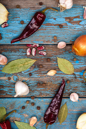 bay leaf: Vegetables and spices on wooden background. Onion, garlic, pepper, bay leaf, beans.