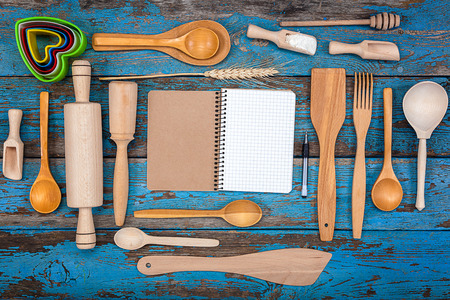 Set kitchen utensils and a notebook for recipes on a wooden background.