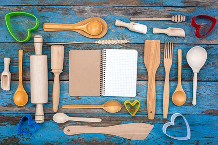 cooking implement: Set kitchen utensils and a notebook for recipes on a wooden background.