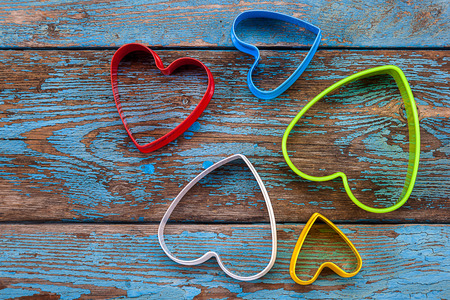 Cookie cutters for baking in the form of heart on a wooden background.