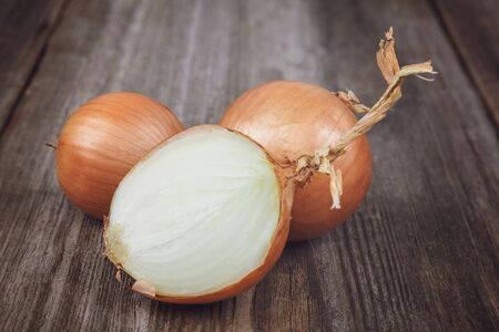 Fresh onions on a wooden background. Stock Photo