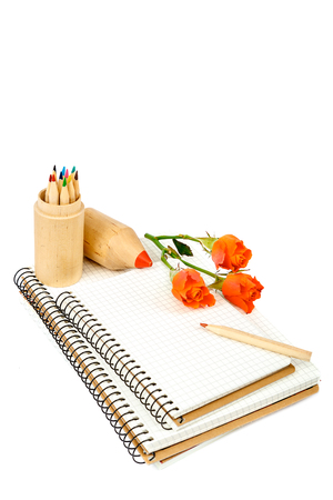 Colored pencils, notebooks and rose flowers isolated on white background.