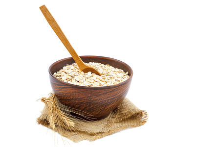 Oat flakes with a wooden spoon and wheat spike isolated on white background. Stock Photo