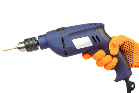 Hammer drill or screwdriver in hand isolated on white background. Stock Photo